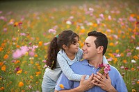 Girl hugging her father in field of flowers
