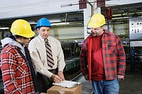 Three people in warehouse reading clipboard