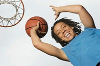 Low angle portrait of teenage girl shooting hoops