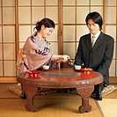 Asian woman pouring tea for businessman