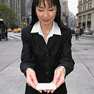 Businesswoman reading card on sidewalk