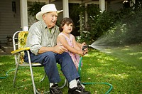 Elderly man sitting in lawn chair helping granddaughter spray water