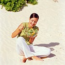 Young woman eating a salad with chopsticks on the beach.