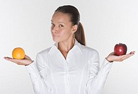 Portrait of woman balancing orange and apple in hands