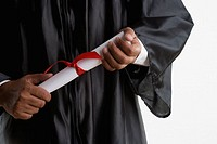 Mid section of man in graduation gown holding diploma