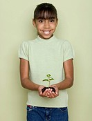 Portrait of girl holding dirt and plant in cupped hands