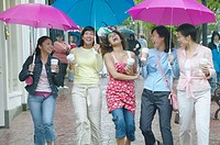 Group of women walking and laughing with umbrellas