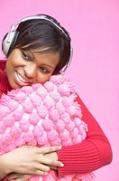 Woman with pillow wearing headphones