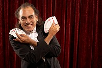 Portrait of magician with cards fanned in hand