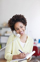 Young woman taking notes over the phone