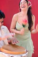 Woman dancing while man plays conga