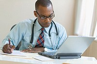 Male doctor filling out paperwork while working on laptop