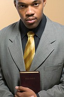 Portrait of man in suit holding Bible
