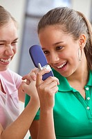 Two teenage girls text messaging on cell phone
