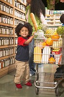 Young African American boy with mother in health food store