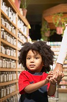 Young African American boy holding mother´s hand in health food store