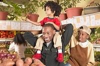 African American father with young sons in supermarket