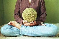 Woman sitting with astroturf ball