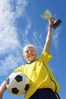 Girl (10-12) holding soccer ball and trophy, portrait, low angle view