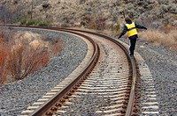Boy walking on railroad track. Washington State. USA