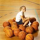 Girl (8-10) sitting on basketballs in gym, portrait