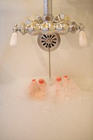 Woman lying in bathtub, feet visible through bubbles