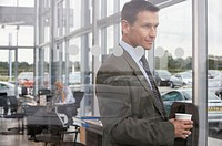 Businessman in car showroom holding drink, smiling, view through glass