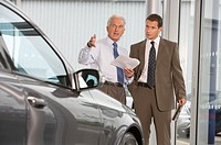 Mature salesman showing businessman car in showroom