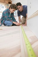 Father and Son Measuring Wood for Baseboard