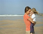 Mother embracing daughter (2-4) on beach, smiling