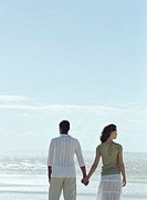 Couple holding hands on beach, facing ocean, woman looking to side