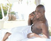 Man wrapped in towel using mobile phone, leaning on elbow, smiling