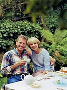 Couple having tea at garden table, smiling, portrait