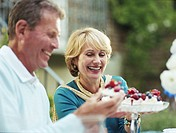 Man taking piece of cake from plate held by woman