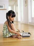 Girl (4-6) sitting on floor sweeping up crumbs into dust pan