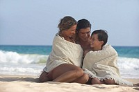 Parents and son (8-10) wrapped in towel on beach, smiling