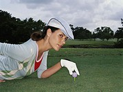 Woman lying on grass, placing golf ball on tee, portrait, side view