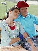 Couple sitting in golf cart, smiling
