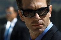 Close Up of a Tough Businessman Wearing Sunglasses and a Businessman in the Background