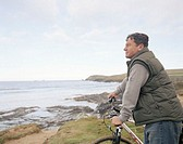 Mature man holding bicycle handle bars, overlooking sea, side view