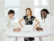 Woman flanked by two men standing by laptop, portrait