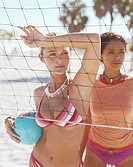 Woman holding ball by friend, hand on volleyball net