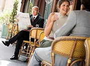 Mature businessman sitting outside cafe reading newspaper