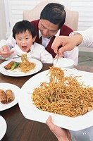Mature man at table with grandson (3-5) on lap, man serving noodles