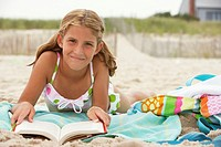 Girl (8-10) lying on beach reading book, smiling, portrait