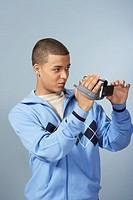 Teenage boy (16-18) using video camera, adjusting viewing window