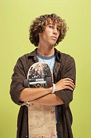 Teenage boy (16-18) with curly hair, holding skateboard, portrait
