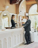 Hotel receptionist greeting businessman, handing key over desk