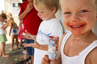Boy (2-4) eating iced treat, face covered in juice, smiling, portrait