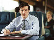 Businessman working on train, portrait (focus on man)
